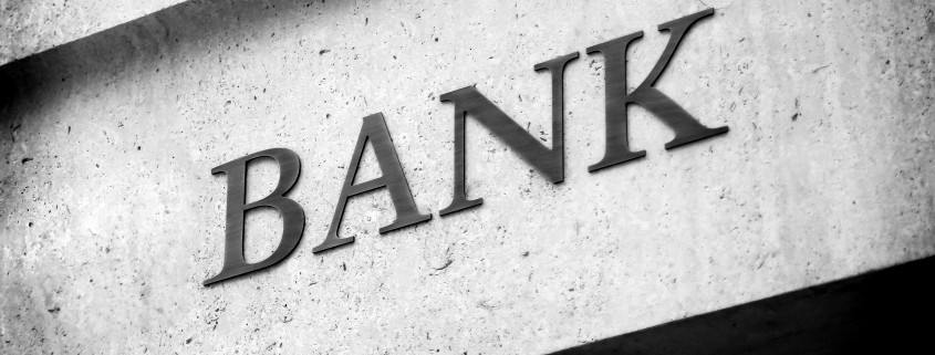 Old fashioned 'Bank' sign on a building exterior.
