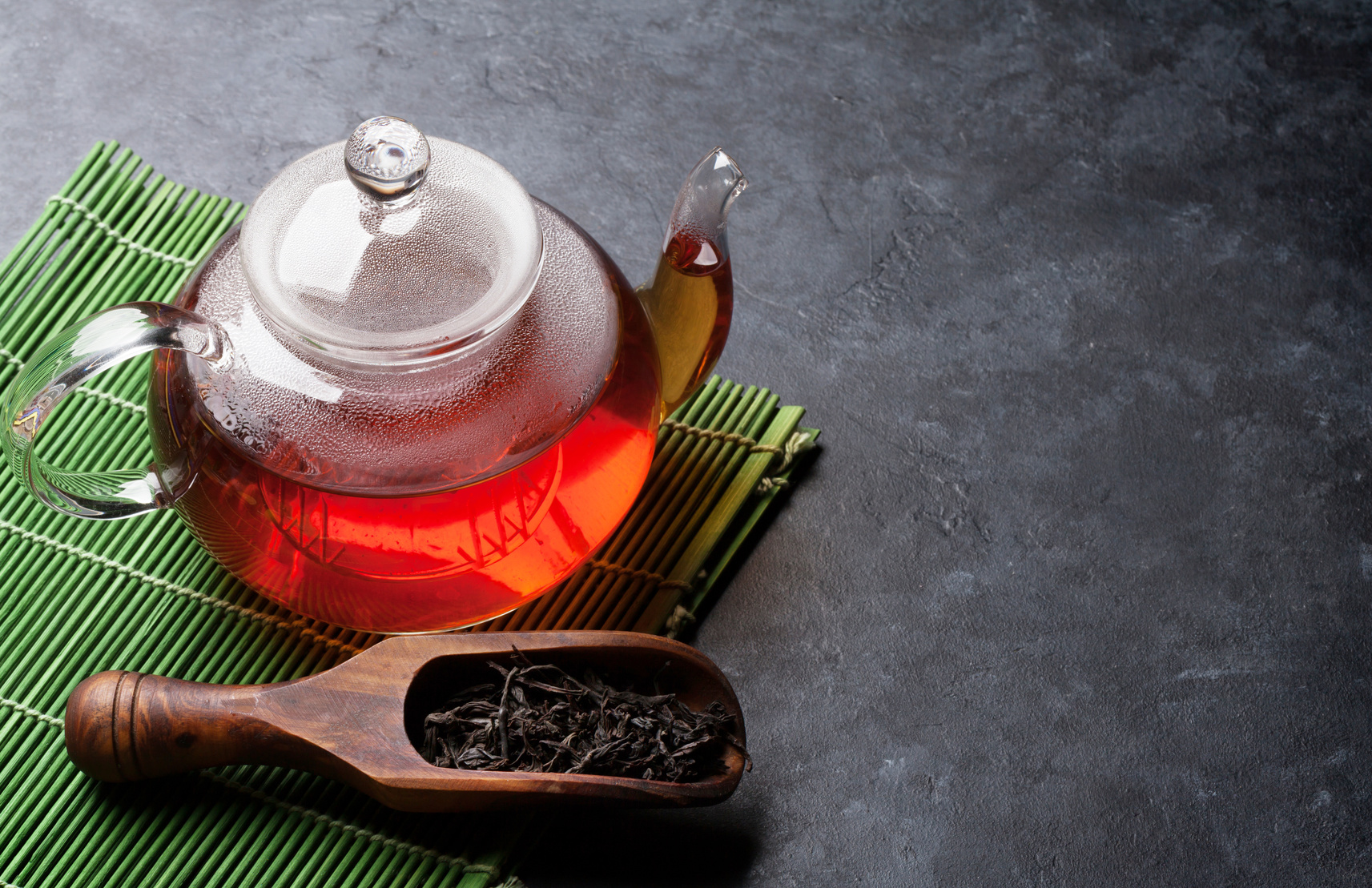 Teapot and dry tea in spoon on stone table. View with copy space
