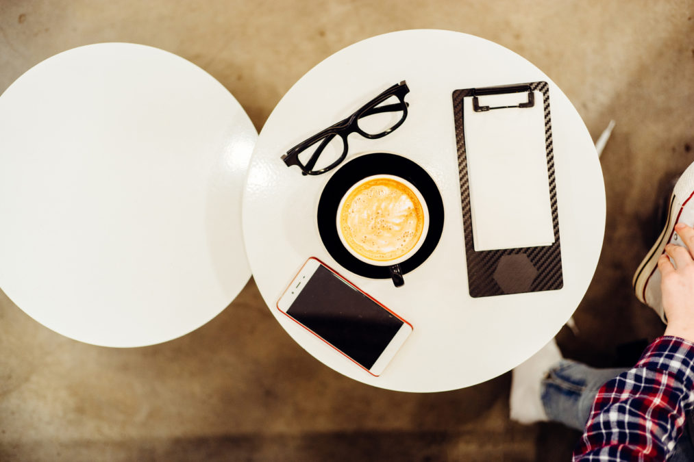 Top view of glasses, cup of cappuccino, clipboard with blank paper and smartphone in modern cafe interior.